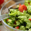 Healthy Chopped Dieting Vegetable Salad Photo. Dish with Organic Cutting Lettuce, Tomato and Cucumber Ingredient in Glass Bowl. Stainless Fork.Home Culinary Food Recipe Partial View Photography